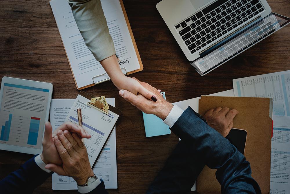 Executivos dando a mão, fechando negócios.