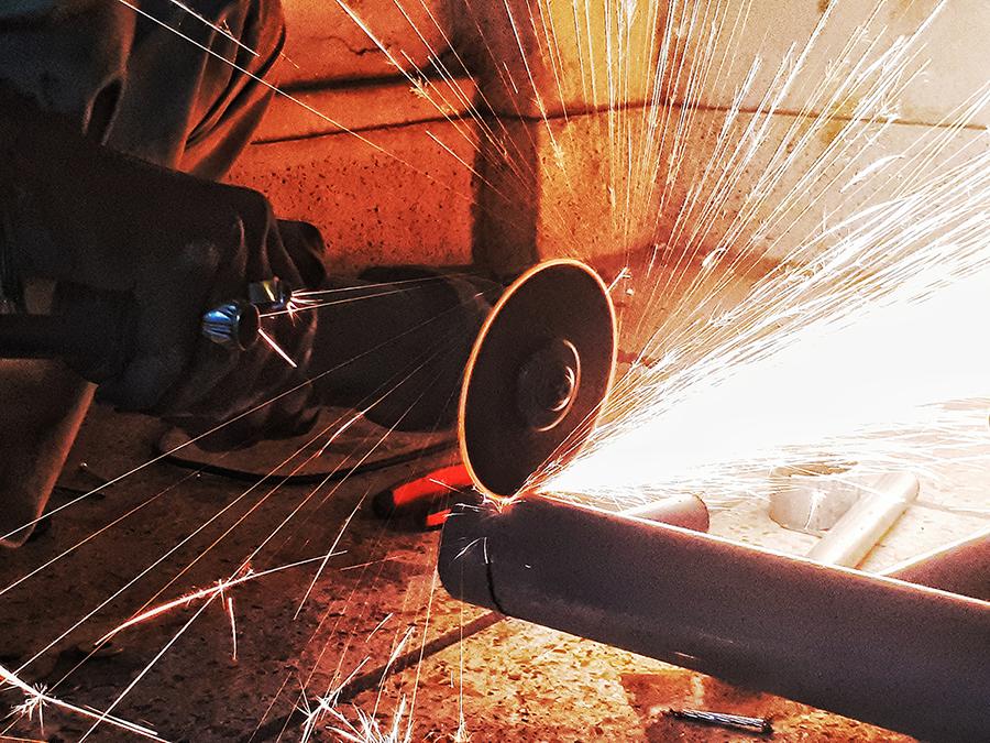 Serra trabalhando em tubo de aço com faíscas saindo, representando consumo do material.
