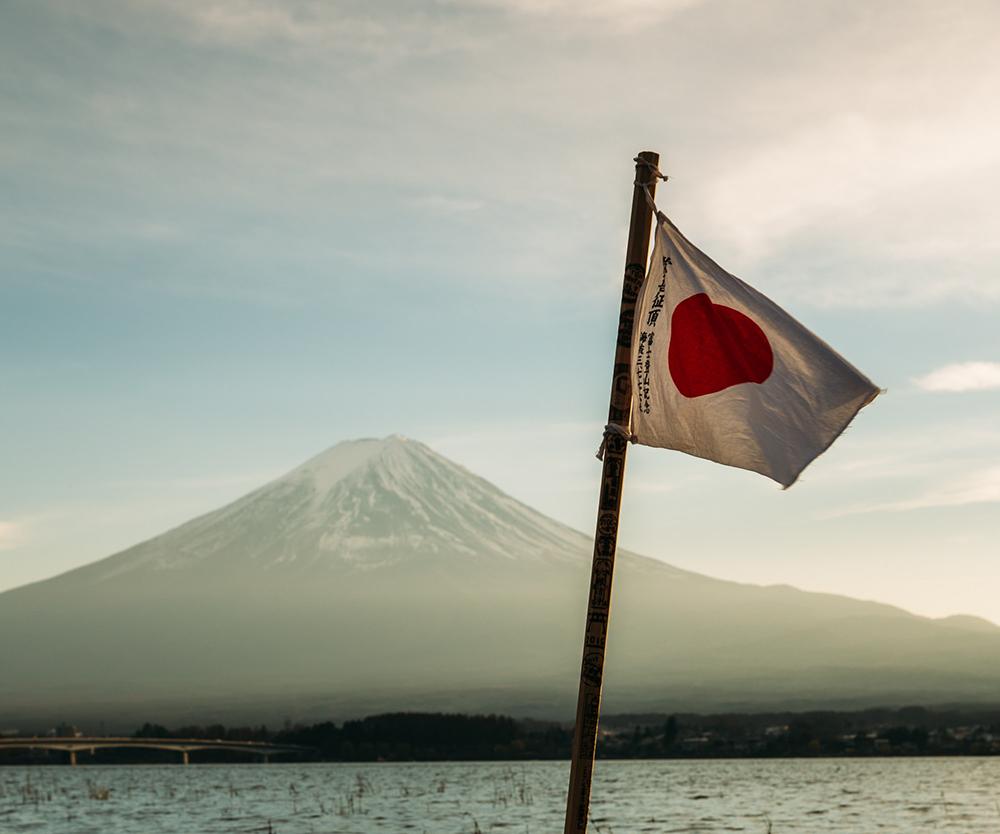 Bandeira japonesa num lago com montanha ao fundo.