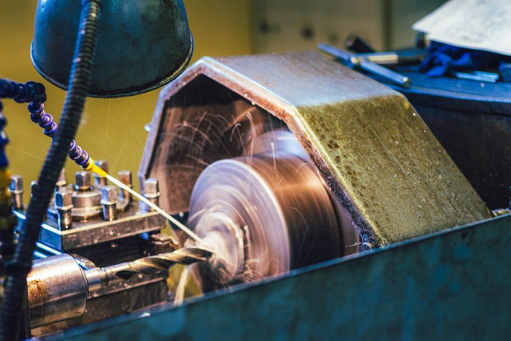 Foto macro de uma máquina de aço trabalhando com faíscas saindo.