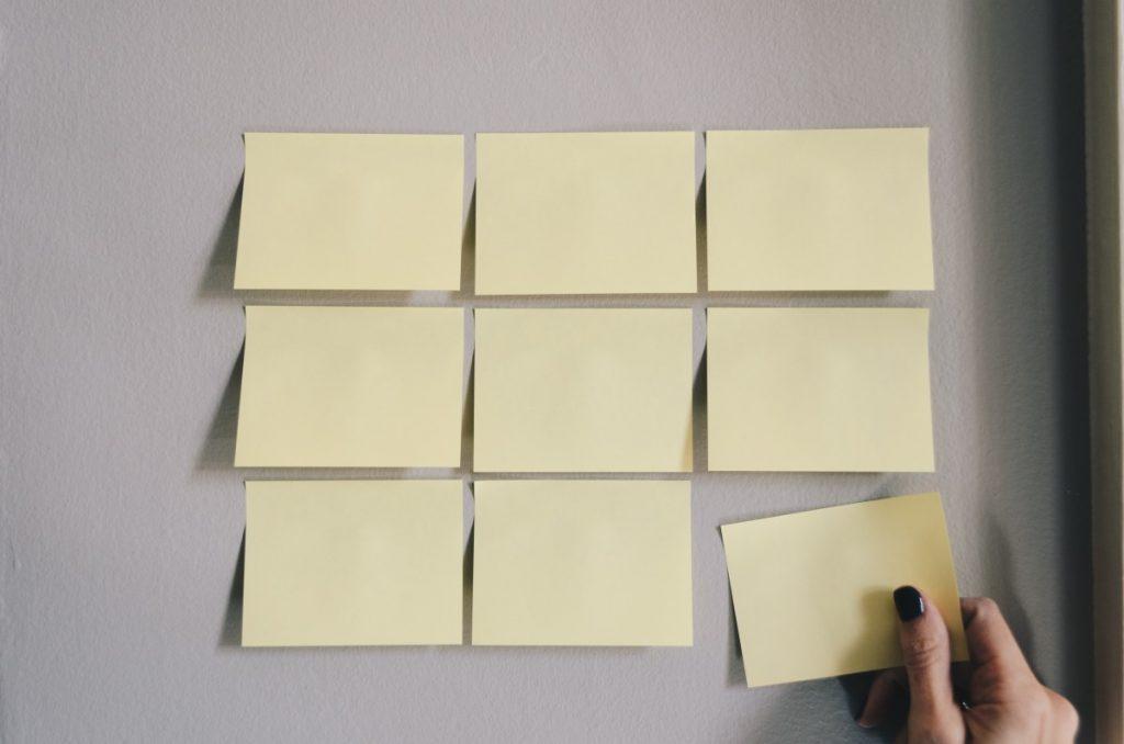 Série de post-its organizados na parede com uma mão colocando o último, representando tarefas a serem realizadas.