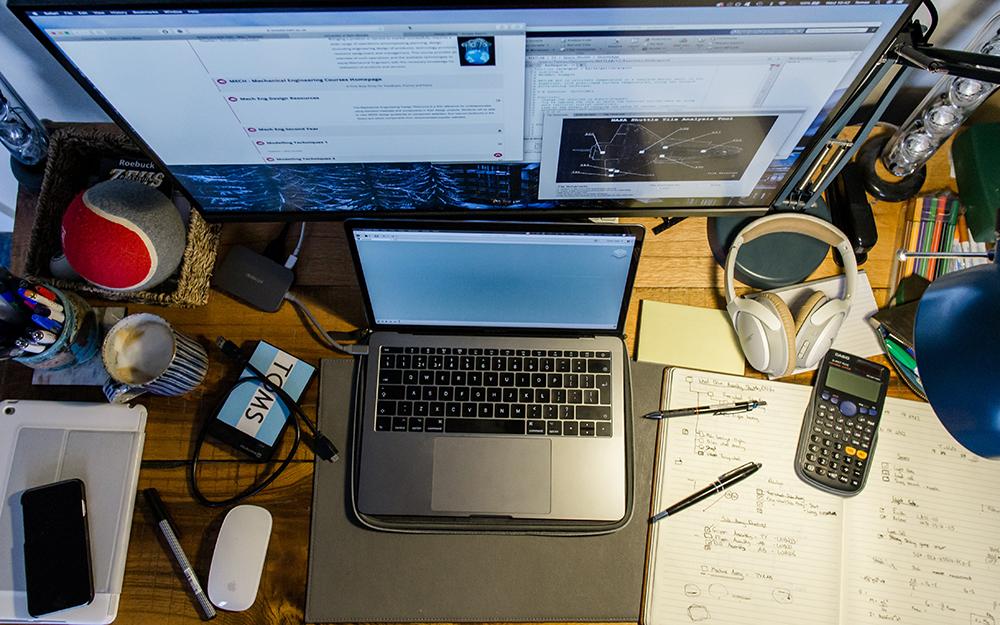 Computadores, anotações e vários dispositivos em uma mesa sobrecarregada.