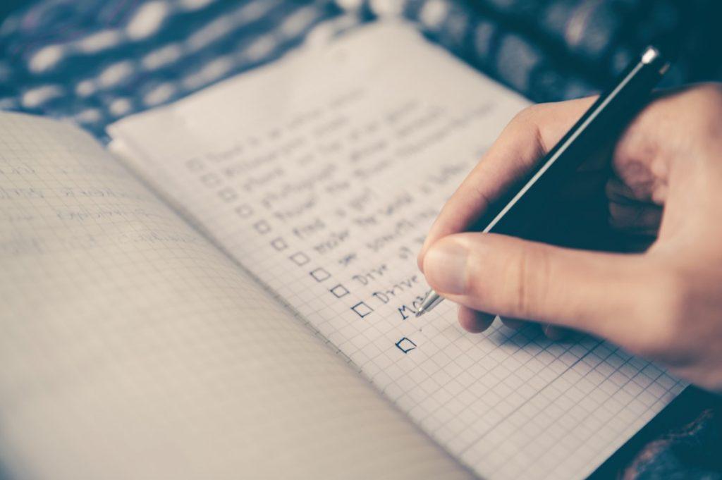 Mão com caneta escrevendo itens num papel planejando o dia para maior produtividade.